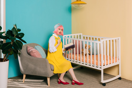 surprised stylish pregnant pin up woman with pink hair holding notebook and looking at camera near baby cot