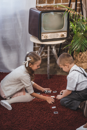 side view of cute kids playing dominoes together at home, 1950s style Stock Photo