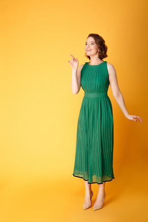 young smiling woman in green dress pointing away isolated on orange Banco de Imagens - 111107322