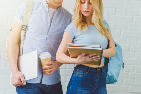 cropped shot of young students working together in front of white brick wall