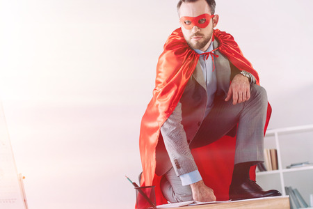 handsome super businessman in mask and cape squatting on table in office