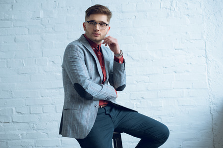 Bearded young man wearing stylish suit sitting in front of white wall Stock Photo