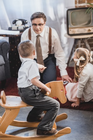 cute little boy sitting on rocking horse and looking at father playing dominoes with daughter, 50s style family
