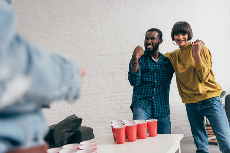 two young multicultural friends doing winner gesture at table with beer pong