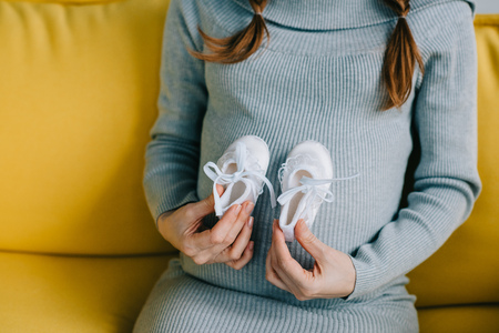 cropped image of pregnant woman touching belly with newborn shoes in living room
