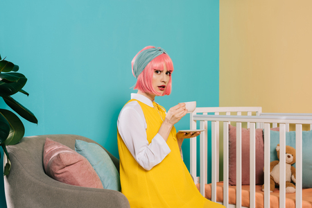 retro styled pregnant pin up woman with pink hair sitting near baby cot with cup of tea and looking at camera