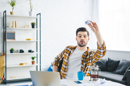 Man throwing crumpled paper while working at home office Stock Photo