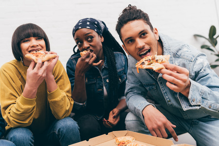 smiling multicultural group of friends eating pizza and watching match Stock fotó