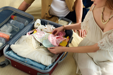 cropped view of pregnant woman and husband packing suitcase for hospital Standard-Bild - 111110697