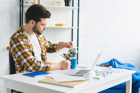 Young man pouring coffee in cup on table with laptop at home office