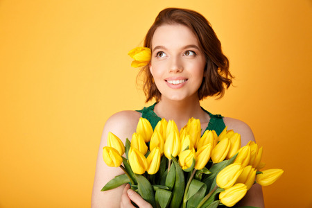 portrait of beautiful woman with bouquet of yellow spring tulips isolated on orange