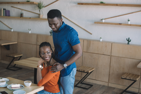 smiling african american man hugging girlfriend on romantic date in coffee shop Stock Photo