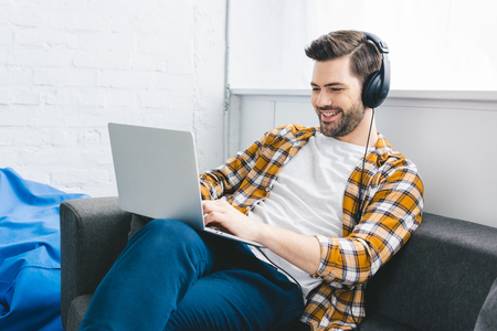 Man in headphones working on laptop in light office