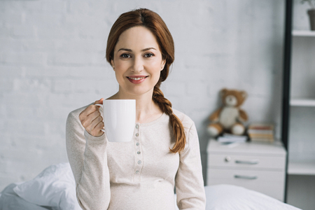 smiling beautiful pregnant woman holding cup of tea and looking at camera in bedroom Stock fotó