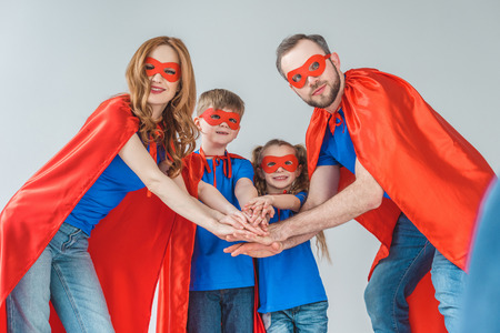 super family in masks and cloaks stacking hands together isolated on grey Imagens
