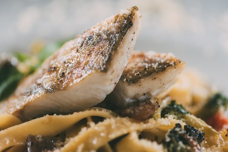 delicious pasta with pike perch fillet, vegetables and parmesan cheese Stock fotó
