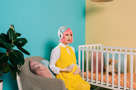 retro styled pregnant woman with pink hair listening music with smartphone in child room
