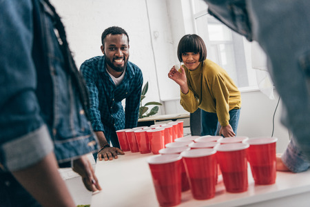 cropped image of multicultural group of friends playing beer pong at table