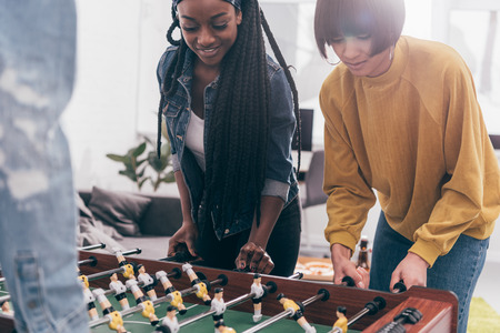cropped image of smiling multicultural friends playing table football Stock Photo