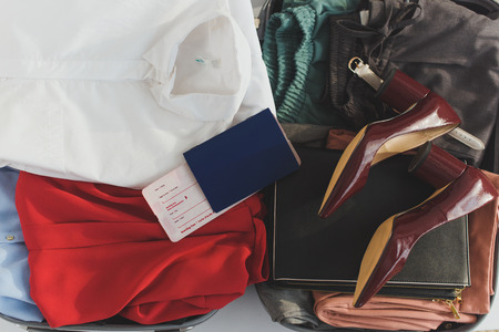 top view of opened travel bag with clothes, heels and ticket with passport