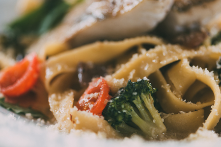 selective focus of gourmet pasta with pike perch fillet, vegetables and parmesan cheese Stock fotó