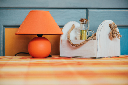 close-up view of decorative orange lamp and wooden box with spices on table in restaurant