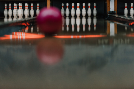 red bowling ball rolling to pins by alley