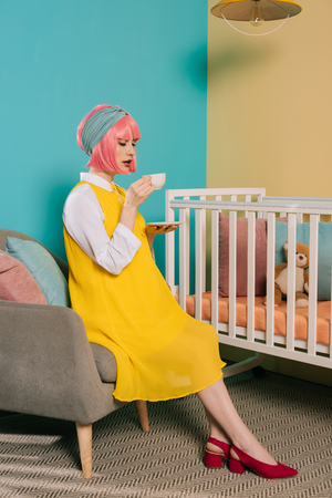 retro styled pregnant pin up woman with pink hair drinking tea near baby cot in child room Stock Photo