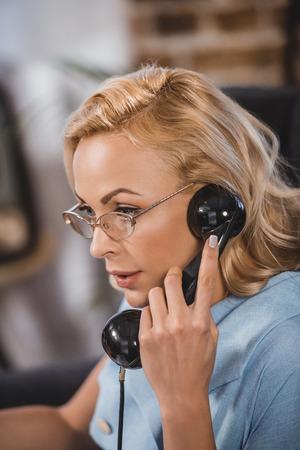 beautiful blonde woman in eyeglasses talking by vintage telephone and looking away
