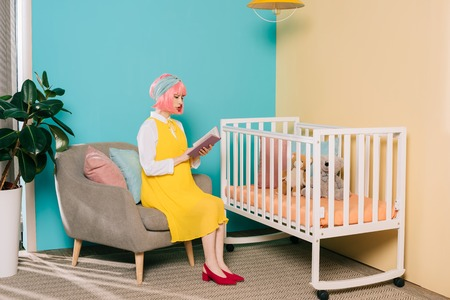 retro styled pregnant pin up woman with pink hair reading book near baby cot in child room Stock Photo