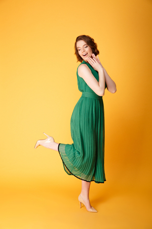 young smiling woman in green dress posing isolated on orange Stock Photo