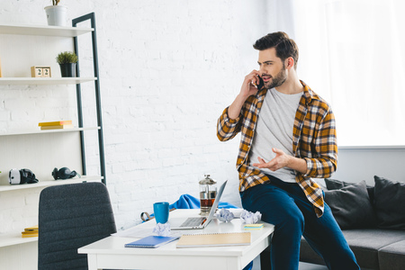 Young man sitting on table and talking on phone in light office Stock Photo