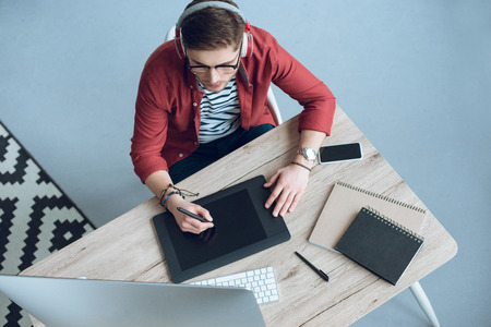 Young man in headphones using graphic tablet by table with computer Stock fotó