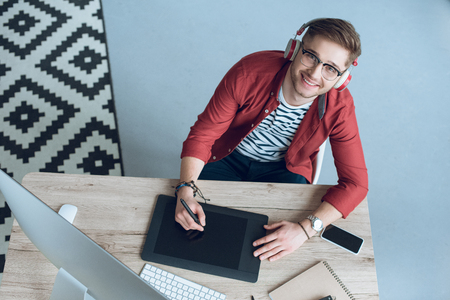 Smiling man drawing with graphic tablet on table with computer at home office