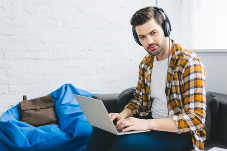 Smiling man in headphones working on laptop in light office Stock Photo