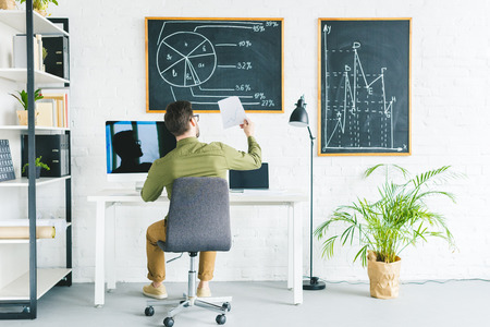 Young businessman working by computers at home office