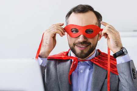 super businessman in cape tying red mask in office Stock Photo