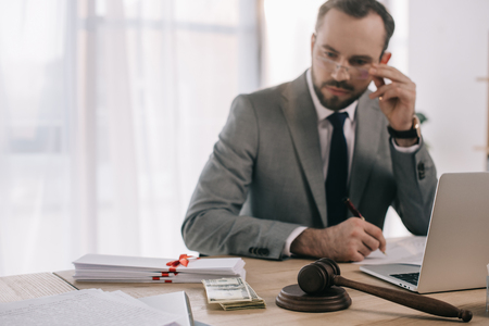 selective focus of lawyer in suit looking at money at workplace with laptop in office Zdjęcie Seryjne