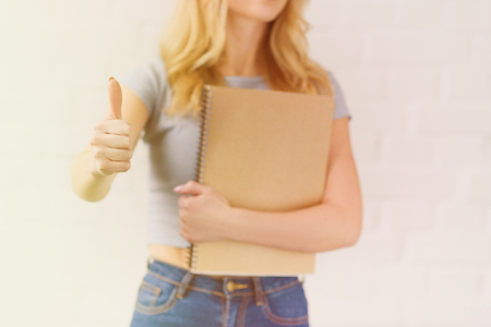 cropped shot of young student girl with notebook showing thumb up Stockfoto