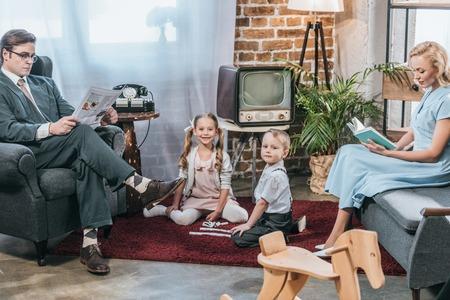 Padres leyendo libros y periódicos mientras los niños juegan con dominó y sonríen a la cámara, estilo retro