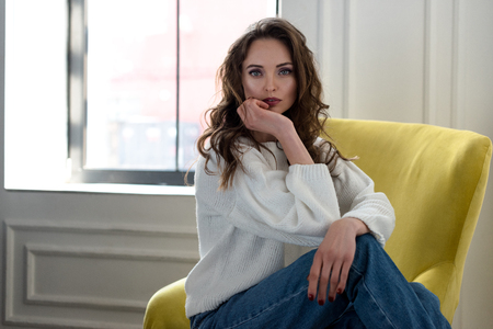 beautiful brunette woman in white sweater and jeans sitting on armchair and looking at camera