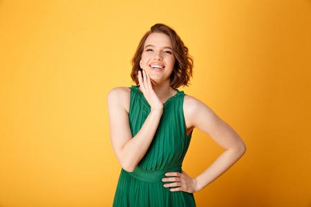 portrait of young smiling woman akimbo isolated on orange