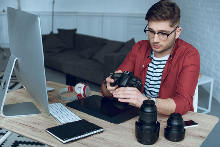 Man freelancer with camera in hands at work by table with computer and graphic tablet Stock Photo