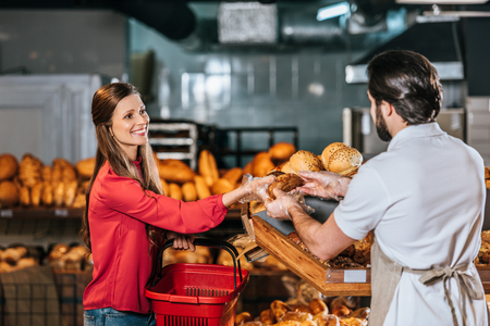 shop assistant giving loaf of bread to smiling woman in supermarket