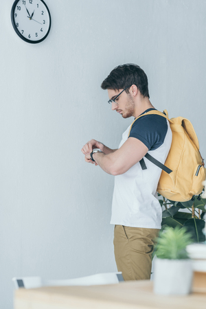 handsome male student with backpack looking at wristwatch