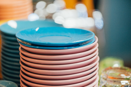 close-up view of stacked clean blue and pink plates in kitchen Banco de Imagens