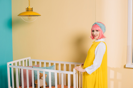smiling retro styled pregnant pin up woman with pink hair standing near baby cot in child room Stock Photo
