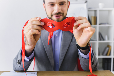 super businessman looking at red mask in office