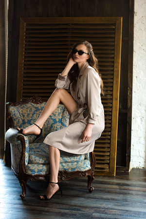 beautiful sexy woman in sunglasses and classic trench coat posing on armchair Stock Photo