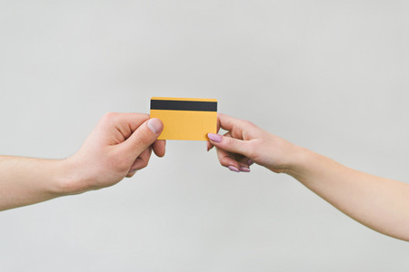 cropped shot of man and woman holding golden credit card isolated on white